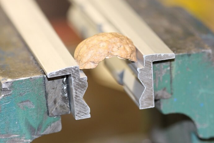 Soft jaw application: Close-up of a walnut shell on the 90 degree heel of the jaws