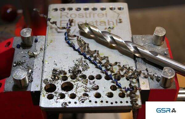 Drilling in metal: metal twist drill (Split Point), stainless steel plate with drill holes and metal chips