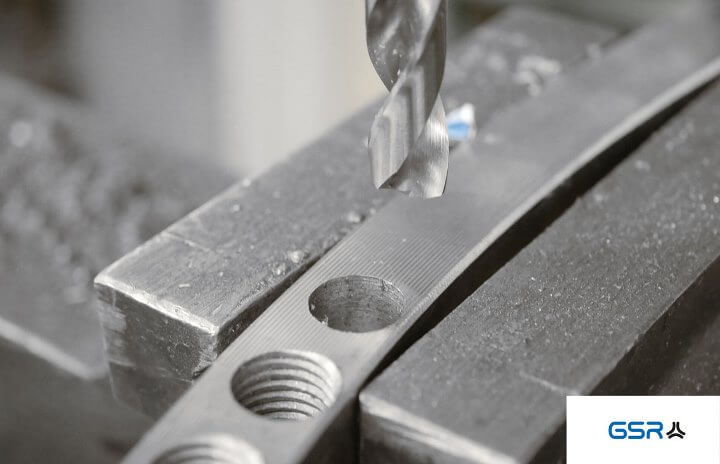 Drilling in metal: Detail of the tip of a metal twist drill with split point after a core hole has been drilled into the workpiece. Core hole and tapped hole can be distinguished very well