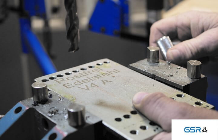 Preparation for drilling in metal: stainless steel plate clamped in vice with twist drill