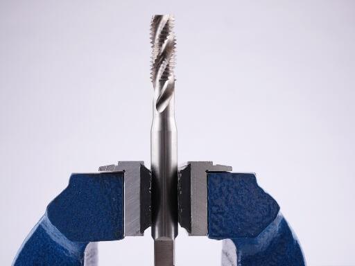 Seitenansicht eines eingespannten Maschienengewindebohrers zwischen zwei Schonbacken aus Aluminium und Gummi-Profils im Schraubstock