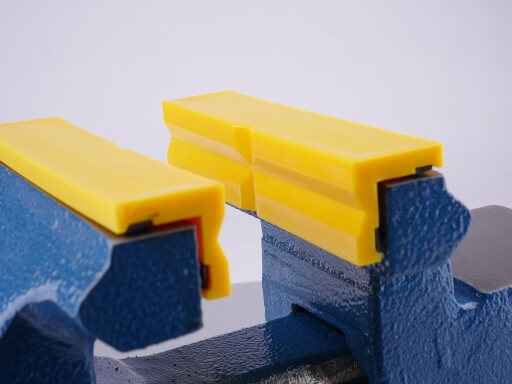 yellow plastic jaws with prism profile clamped in vice