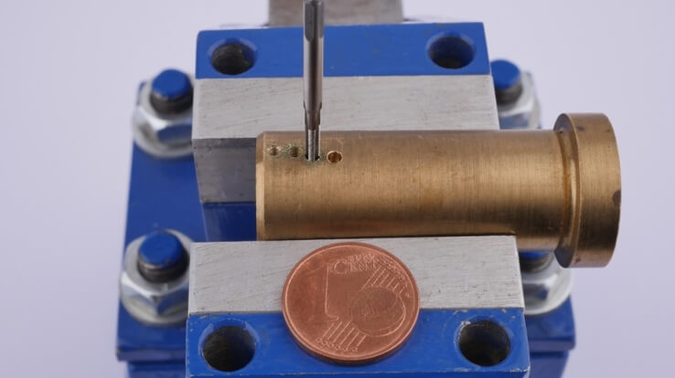 lose-up: Cut a thread in the pipe with the miniature tap. The 1 cent piece is for comparison