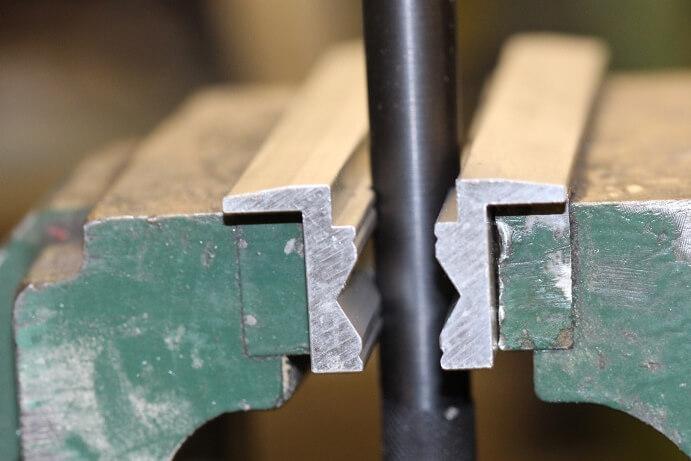 Nahaufnahme eines senkrecht eingespannten Rohres zwischen Alu-Prismen Schonbacken und Schraubstock
